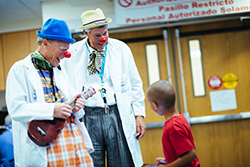 Hospital clowns laugh with a child.