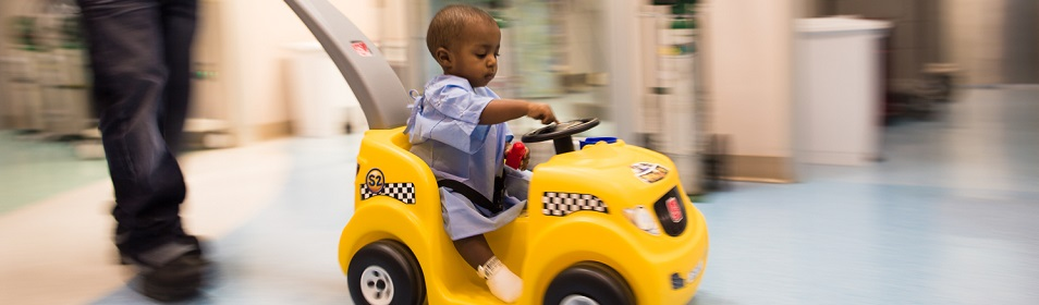 Boy in a toy car making his way through the hospital