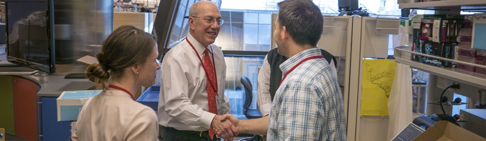 President and CEO Kurt Newman shakes a researcher's hand.