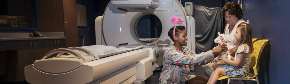 family and nurse smiling outside MRI machine